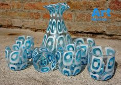 Product Description  Production: Hand blown glassware made in Murano, Italy Artist: Certified Murano master glassmaker Delivery: 14 days (made to order artwork) Dimensions: drinking glass: 10cm (3.9 inch) height ~ 8cm (3.1 inch) diameter; carafe: 40cm (15.7 inch) height Quantity: 6 glasses and 1 Carafe Authenticity: signed, labeled, certificate of origin is provided  Murano Glass Pitcher & 6 Drinking Glasses  Expertly hand crafted in Italy, the displayed Murano Glass Pitcher & 6 Drink...