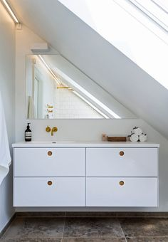 Sloping wall in the bathroom? Make use of it by getting or creating a mirror that fits into the slope.