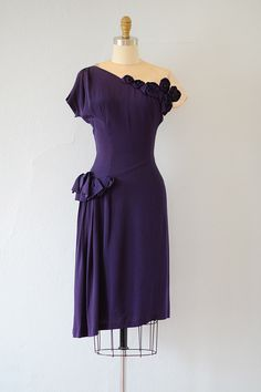 Stunning 1940s dress with nude sheer detail on the bodice. Dress features purple rosettes decorating the left side of the upper bodice that extends to the back and ruffle and pleat draping on right hip. Slightly asymmetrical. Via Adored Vintage.