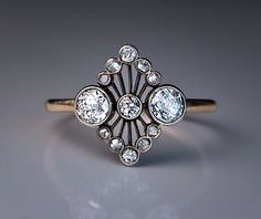 An Antique Openwork Ring Made in Moscow between 1908 and 1917. This elegant Belle Epoque silver topped 14K gold ring is set with three old European cut, two single cut and eight rose cut diamonds.