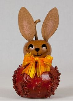 """Introducing Gloria, our new springtime bunny. Gloria is available in 3 styles, all featuring our new brown bunny head with a bright bow. The warty gourd bunnies are available in purple or orange and are about 5"""" in diameter. The tall brown bunny has a natural colored belly and is about 12"""" tall. These bunnies are excited to be added to your spring décor."""