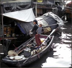"""One of Macau's """"Boat People"""" standing with her child aboad a sampan."""