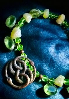 Celtic Glow Some colors are hard to match, are challenging, defiant. This mix has that lime -ish green intense and voluptuous almost Royal that needed to be honored. Old Vaseline real beads, that ones that glow with certain light and are amazing share the stars with a green lime-ish roman glass bead, and… light peridot like stone aged and oxidized silver plated OOAK custom made to me- pendants, all oval except one, in that passion of mine to create with elements that break tradition ...