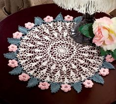 Roses & Leaves Free Doily Crochet Pattern. Breathtakingly gorgeous in its lacy finery and intricate design, this creamy, off-white doily edged in petal pink roses and sage green leaves adds an aura of soft beauty wherever you place it. Skill Level Intermediate Finished Size 13 3/4 inches in diameter Materials Size 20 crochet cotton: 120 yds ecru 90 yds sage 90 yds pink Size 10/1.15mm steel crochet hook or size needed to obtain gauge Free Pattern More Patterns Like This!