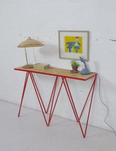 This is a slim sculptural steel console table called Giraffe. Designed by &New and made in Britain.