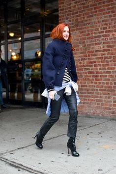 Taylor Tomasi Hill in a navy jacket, striped top, black leather pants and black high heels.