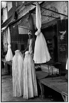 Henri Cartier-Bresson // Pakistan, 1948 - - Two ladies in purdah at a bazar where war surplus parachutes are being sold for clothing material.