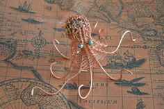 Wire wrapped octopuss in copper and turquoise made by La Roue des Fay