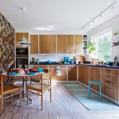 not into that wall on the left, but loving how simple this is yet fun. White bases for the cabinets with wood doors and clean handles, works well with white, stainless, or even colorful appliances. Danish Kitchen, Scandinavian Kitchen, Home Interior, Interior Design, Functional Kitchen, Swedish Design, Kitchen Colors, Kitchen Ideas, Mid Century House