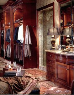 Grand walk in men's closet with custom wood built-ins, marble flooring of a luxury Traditional English Manor in Dallas, Texas
