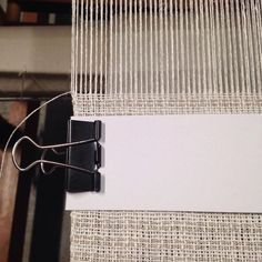 """For my fellow weavers: On a recent warp I struggled a lot with the selvedge, either breaking warp threads or getting wobbly results. I first tried a temple but it just doesn't suit me. So I came up with this workaround and it helped a lot. I just folded an 8"""" strip of narrow card stock around the selvedge and secured it with a binder clip, one on each side. I shared this already with @mloomco and she seems to like it too. If you try it yourself, let me know about your results. Thank you!"""
