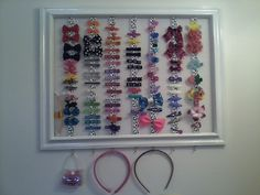 I just finished this, got the idea from a similar Pinterest Pin.  Bought frame at Michael's crafts  and painted it a high closs white, two spools of ribbon from thier dollar bin and a white bandana (hard to see in this photo against a white wall.) I stapled the ribbon on the back, then the bandana creating a backing.  Hooked it up with mounting brackets and C hooks along the bottom.  I love it!  It's the prettiest way to see all my daughters hair accessories.  They had been in a zip lock…
