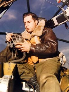 While still the ground at an unspecified base, American Captain Louis Detoni adjusts his oxygen mask as he sits in front of what appears to the bombardier's position in the nose of heavy bomber, England, (Photo by PhotoQuest/Getty Images) Ww2 Aircraft, Military Aircraft, Fighter Aircraft, Nose Art, Second World, Oxygen Mask, Colour Images, Us Army, Colorful Pictures