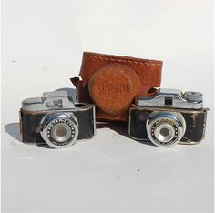 """two vintage mini """"spy"""" """"hit"""" type mini cameras and one leather case Starlight and Arrow brands, via Etsy."""