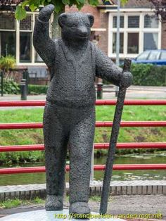 """""""Bruintje Beer"""" (Rupert Bear) sculpture in Musselkanaal, The Netherlands - photo from standbeelden.vanderkrogt;  Rupert Bear is the main character in a comic strip that began in 1920, drawn by Mary Tourtel. The bear is dressed in a sweater, checkered pants, and a scarf. Branbergen (a cookie company in Musselkanaal) has made cookies since 1920 that look like Rupert."""