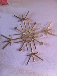 DIY Christmas snowflake craft. Another one if this years family Christmas crafts. Popsicle sticks, hot glue and spray paint. To make the little circles I cut thin pieces crossways from a small fireplace log.