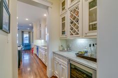 441 24th St A Houston, TX 77008: Photo Butlers Pantry equipped with a stainless steel wine fridge, marble countertops and backsplash, built-in wine racks and display cabinets.