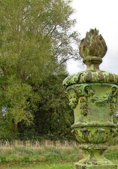 Interesting juxtaposition of an elaborite rococo urn against a background of what appears to be an abandoned field with a very prosaic wire fence