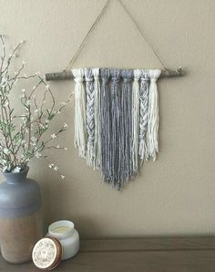 Very simple, yarn tied to a stick creates an attractive and inexpensive wall hanging.