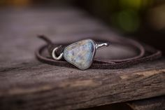 An irregular hand shaped opal wrapped in sterling silver paired with a strap of brown sueded leather.1'x.75""