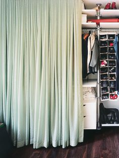 The contents of the 15-foot-long closet are concealed by a long swath of calming blue-green fabric that glows like a light box when illuminated from within.