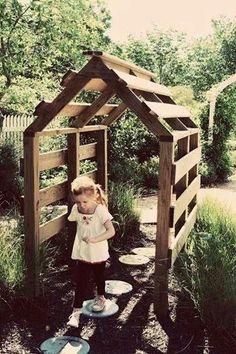 Een houten kas of speelhuisje in de tuin van pallets.