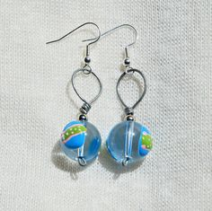 This is a pair of wire wrapped earrings. They have clear spheres with egg shapes on them!