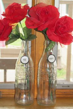 Decorating with Coca Cola Bottles and red flowers for my Coca cola themed kitchen. Also I like the added touch with the Mr. and Mrs tags on the bottles.