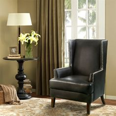 Taking a transitional wing chair and making it more contemporary with this rich black bonded leather and silver nail head treatment, makes this chair a definite show stopper.