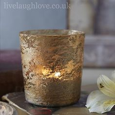 This is a rustic ribbed glass tea light holder, which would be perfect for a golden anniversary or wedding party table decoration. This tealight has a hint of green colour in it which allows the light to glow through giving it a warm golden glow.