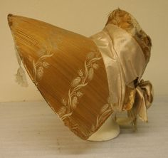 Woman's bonnet, large yellow straw, straw laid in horizontal pieces, three bands of white woven pattern of wheat sheaths across brim and one band across back. Light pink or white wide silk ribbon around back forming ties, white silk lining. From the Pennypacker collection, Philadelphia. ca. 1820