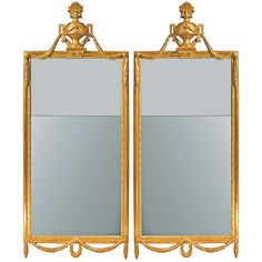 An elegant pair of Italian 19th century Louis XVI st. giltwood mirrors ;  with bottom swaging berried laurel garlands held by mottled circular buttons and inner beaded borders. Topped with central reserve of richly carved urns with foliage. The urn with handles decorated by swaging berried laurel garlands held by the same mottled circular buttons - Dim: 6 ft. 2 in.Hx29.25 in.Wx4.5 in.D // 188 cmHx74 cmWx11 cmD.