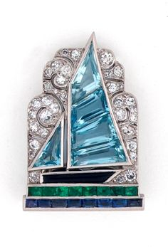 Art Deco diamond and gem-set sailboat clip by Cartier, the fancy-cut aquamarine sailing boat with black onyx hull on a bufftop emerald and sapphire sea against
