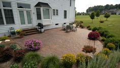 ground level stamped concrete patio surrounded by shrubs and plants.