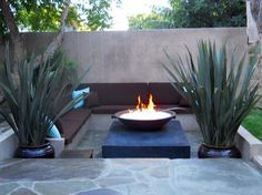 Even a small yard will feel bigger if it is terraced or multileveled. This recessed living space focused around a fire pit and set off with large planters seems like an exclusive inner circle in which you need a special invite.