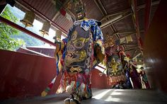 Monks wearing magnificent costumes and masks perform prayers before the Thangka, or traditional painting of Lord Buddha, is unveiled at a Tibetan temple during Vesak day celebration in Ipoh, Malaysia