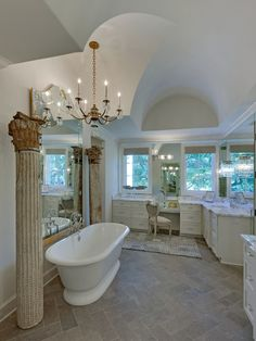 Pink Ribbon House: Arched ceilings, plenty of windows and a light-reflecting vintage mirror (near the free-standing bath tub) create an elegant atmosphere for the master bath. Antique columns from France at each end of the tub designate the soaking area.