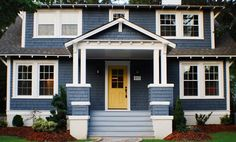 Dusty blue traditional home exterior with yellow door
