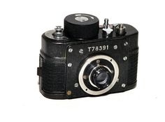 """The F21 was allegedly used by the  KGB for espionage purposes and made in the Krasnogorsk factory in Moscow from the 1960's - 1980's . It takes the form of a miniature """"Robot"""" style camera with clockwork motor drive. 21mm wide un-sprocketed film is held in special cassettes giving an 18mm x 24mm frame size. Variations exist with CDS auto metering.  It has also been found in various disguises and a remote release  The version above was made in 1978 and is the basic camera."""