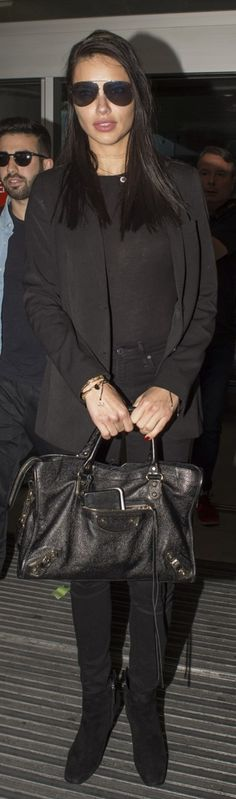 Who made Adriana Lima's black handbag, suede ankle boots, skinny jeans, and aviator sunglasses?