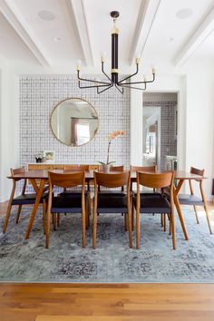 Midcentury-modern inspired dining room with a statement chandelier, midcentury chairs, and a round mirror