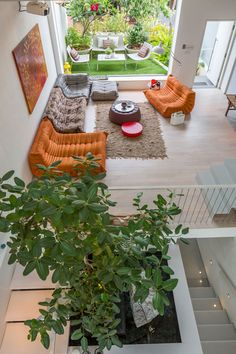 Get some interior design ideas by looking at 15 living room layouts from above // The painting on the wall ties all the colors in the living room together and makes the orange seating blend in with the rest of the decor.