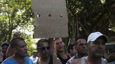 """A Cuban migrant holds a sign that reads """"We demand human rights for Cubans"""" at the border between Costa Rica and Nicaragua in Penas Blancas on 17 November, 2015."""