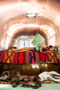 Tiny home living. Airstream. Two dogs. Books and blankets.  Photo by @thenoisyplume