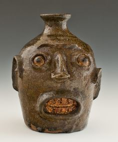 Face jugs are stoneware vessels... eyes and the teeth are made of kaolin. They were created by slaves in the Edgefield District of South Carolina in the second half of the 19th century, and were produced for a period of only about 30 years.  ...The jug's form suggests that it is early, probably from around 1862.