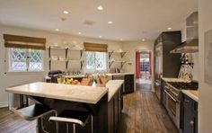 """Jen Aniston's rented home's kitchen...not so sure how it """"fits"""" --in many senses of the word--in this house. Strange shapes and cold material choices. Interesting use of space though, that's why I am featuring it."""