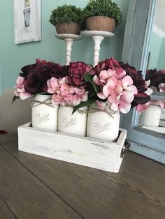 Mason jar centerpiece with distressed white box and jars and pink/red flowers