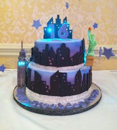 NYC Sweet 16 cake! - This cake was created for a NYC sweet 16 theme. The cake was covered in whit fondant and then airbrushed in pink, purple, and blue. The buildings are fondant and the statue and empire state building are modeling chocolate. Small battery powered LED lights were used in the empire state building, behind the statue, and in the buildings on top. Thanks for looking!
