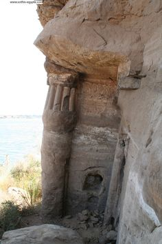 Under the natural rock, a water lily bud column and a wall from the ruins of the Chapel of King Seti I, overlooking the river Nile. 19th dynasty. Rock temple of Gebel Silsileh. Upper Egypt, near Aswan and Edfu. 18th-19th dynasty, reigns of Kings Horemheb, Rameses II, and Merenptah.