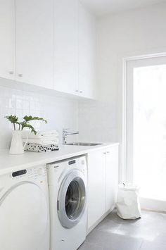 Modern white laundry room features white cabinets paired with white countertops and a white grid tiled backsplash.